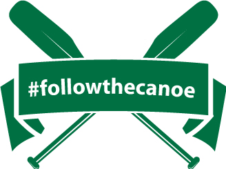 Crossed paddles with banner that reads follow the canoe.